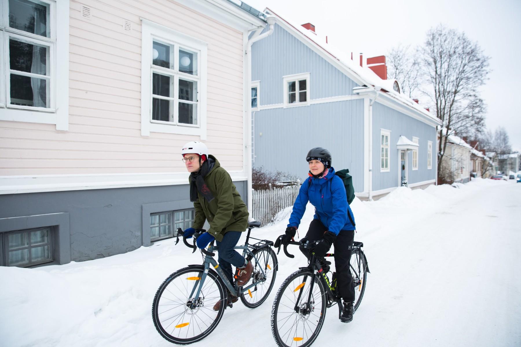 A man and a woman bike down a snowy street.