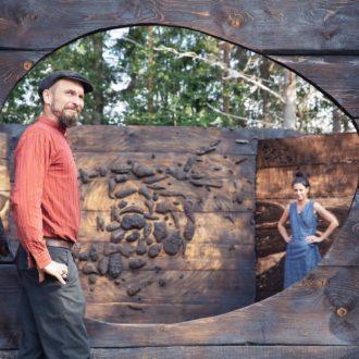 Um homem e uma mulher estão entre painéis de madeira e esculturas em um parque.