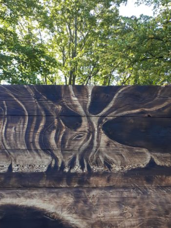 Wooden panels with designs on them stand in front of leafy trees.