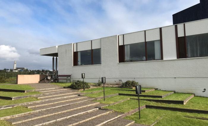 Широкая лестница спускается от низкого прямоугольного здания.