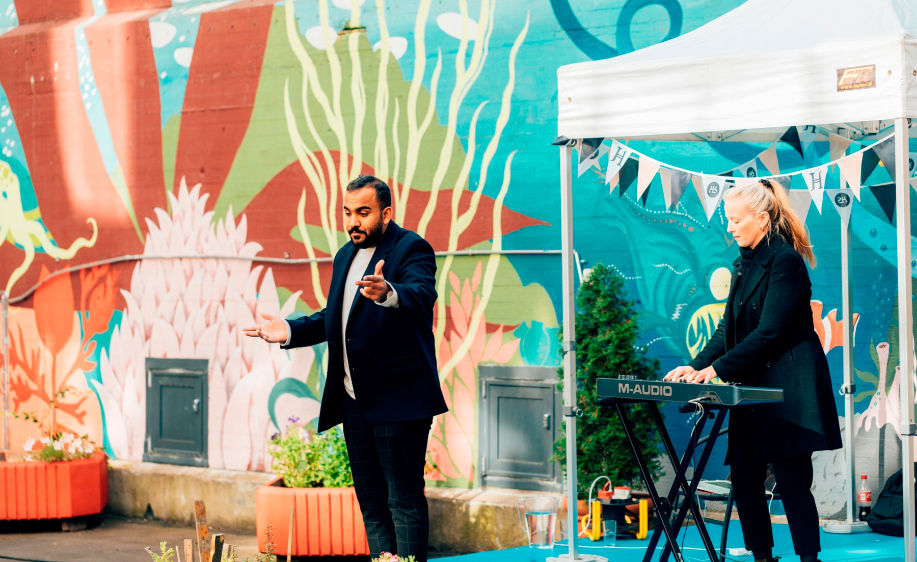 A man sings and a woman plays keyboards outdoors in front a colourfully painted wall.