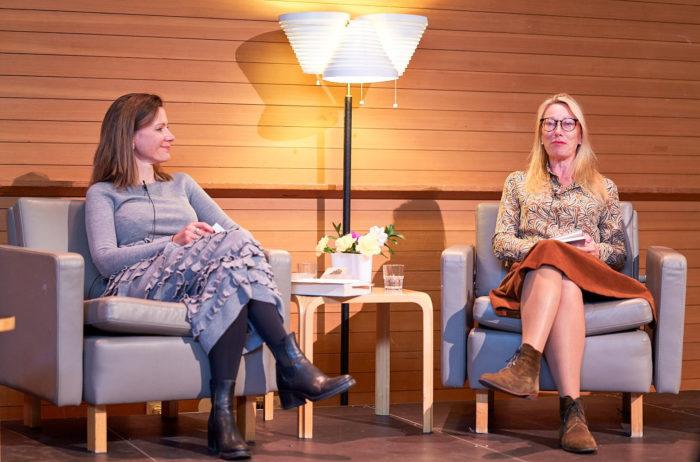 Две женщины сидят в кресле на сцене.